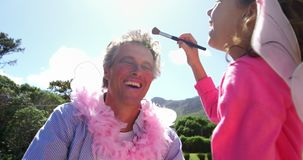 Cute daughter in fairy costume putting makeup on her fathers face 4k. Cute daughter in fairy costume putting makeup on her fathers face at garden 4k stock footage