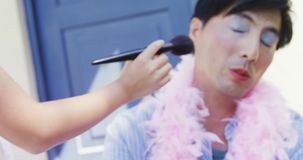 Cute daughter in fairy costume putting makeup on her fathers face 4k. Cute daughter in fairy costume putting makeup on her fathers face at outside home 4k stock video footage