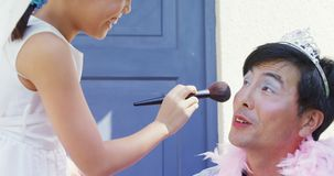 Cute daughter in fairy costume putting makeup on her fathers face 4k. Cute daughter in fairy costume putting makeup on her fathers face at outside home 4k stock footage