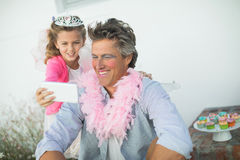 Cute daughter in fairy costume showing mobile phone to father royalty free stock photography