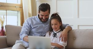 Cute daughter and father having fun watching videos using laptop