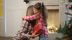 Cute daughter giving Christmas gift to mother stock footage