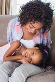 Cute daughter lying across mothers lap Royalty Free Stock Photography
