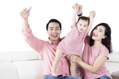 Cute daughter and parents playing on couch Stock Photography