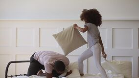 Cute daughter playing pillow fight on bed with black father