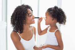 Cute daughter putting makeup on her mothers face Royalty Free Stock Images