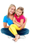 Cute daughter sitting in mother's lap Royalty Free Stock Photos