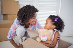 Cute daughter sitting in moving box holding teddy with mother Stock Images