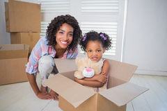 Cute daughter sitting in moving box with mother Royalty Free Stock Photography