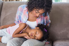 Cute daughter sleeping across mothers lap on the sofa Stock Photography