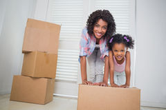 Cute daughter unpacking moving boxes with her mother Stock Photography