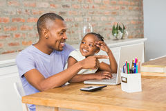 Cute daughter using laptop at desk with father Royalty Free Stock Photography