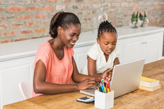 Cute daughter using laptop at desk with mother Royalty Free Stock Photo