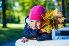 Cute daydreaming girl sitting on the bench with maple leaves in Stock Photos