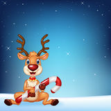 Cute deer holding Christmas candy on a night sky background Royalty Free Stock Photos