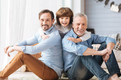 Cute delighted child hugging his father and grandfather. Expressing love. Cute delighted positive child sanding between his father and grandfather and laughing royalty free stock image