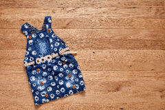 Cute denim dress on wooden background. Royalty Free Stock Photography