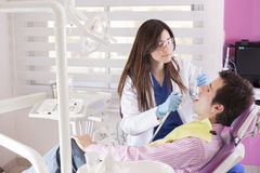 Cute dentist focused at work Royalty Free Stock Photos