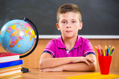 Cute diligent boy sitting in classroom Stock Photography
