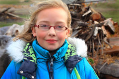 Cute Dimples, Hoody and Wood Pile. A closeup of a cute little blond 9 year old girl wearing glasses and a warm blue winter hoody coat. A wood pile in the Royalty Free Stock Photography