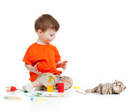 Cute dirty child with paints looking at cat Stock Images