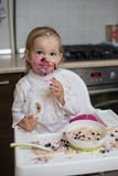 Cute dirty little girl eating healthy porridge. With bilberry with plastic spoon, while sitting in the high chair at table in the kitchen. Image with selective Stock Photography