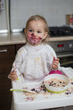 Cute dirty little girl eating healthy porridge. With bilberry with plastic spoon, while sitting in the high chair at table in the kitchen. Image with selective Royalty Free Stock Image