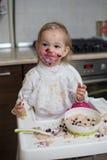 Cute dirty little girl eating healthy porridge royalty free stock image
