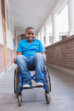 Cute disabled pupil smiling at camera in hall Royalty Free Stock Photography