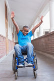 Cute disabled pupil smiling at camera in hall Stock Images