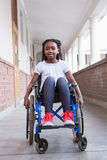 Cute disabled pupil smiling at camera in hall Royalty Free Stock Images