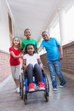 Cute disabled pupil smiling at camera in hall with her friends Stock Photography