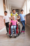 Cute disabled pupil smiling at camera with her friends Royalty Free Stock Images