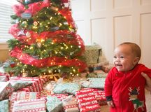 Cute diverse little boy smiling on Christmas morning in front of a Christmas tree Stock Image