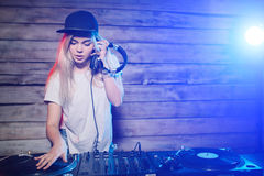 Cute dj woman having fun playing music at club party. Cute dj woman having fun playing music on vinyl record deck at club party nightlife lifestyle Stock Photo