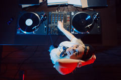 Cute dj woman having fun playing music at club party. Cute dj woman having fun playing music on vinyl record deck at club party nightlife lifestyle. Top view Royalty Free Stock Photos