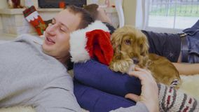 Cute dog chews Santa`s hat. Three young people lays on floor on carpet and relax. People celebrates Christmas and spend their leisure time together at home. Cute stock video