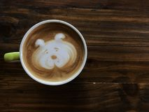 Cute dog face latte art coffee in white cup on wooden table stock images