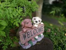 Cute dogs with WELCOME label. Cute little dogs holding label write WELCOME in garden Royalty Free Stock Image
