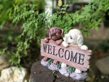 Cute dogs with WELCOME label. Cute little dogs holding label write WELCOME in garden Stock Images