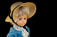 Cute doll that wears a hat and a blue dress. Fine old doll with makeup and nice haircut Stock Image
