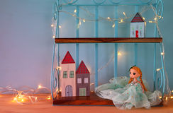 Cute doll and wooden little houses next to warm garland lights in front of blue background. Cute doll and wooden little houses next to warm garland lights in royalty free stock photo