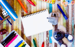 Cute dolls with blank open notebook and crayons on wooden backg Stock Photos