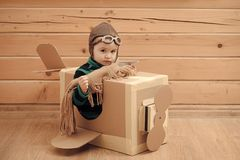Cute dreamer boy playing with a cardboard airplane. Childhood. Fantasy, imagination. Retro style royalty free stock photography