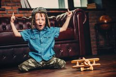 Game with airplane. Cute dreamer boy playing with toy airplane at home. Childhood. Fantasy, imagination Stock Photo