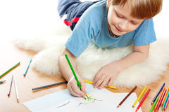 Cute dreaming child lies and draw. On soft sheep fur isolated over white background stock images