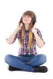 Cute dreaming teenage girl sitting and listening music with head Stock Photography