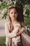 Cute dreamy child girl posing at rustic wooden fence with teddy bear stock photo