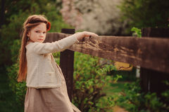 Cute dreamy kid girl in beige outfit climbing rustic wooden fence in spring garden Stock Photo