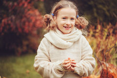 Cute dreamy kid girl in warm knitted sweater and scarf playing in the garden in late autumn Stock Image